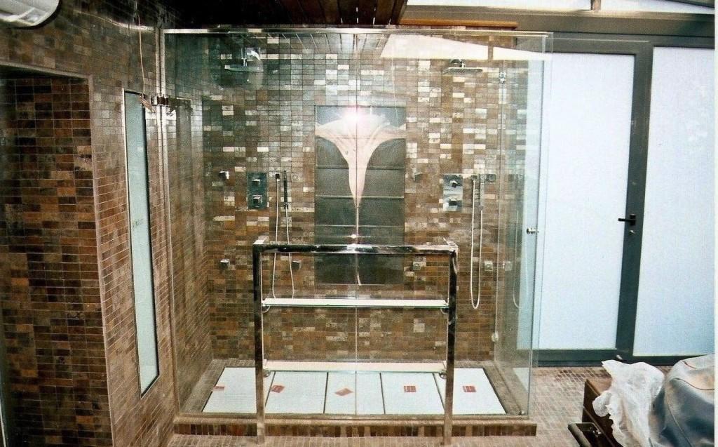 Cabina de dutxa artesanal composta per vidre lateral fix i porta d'entrada practicable, suport de subjecció tipus tovalloler