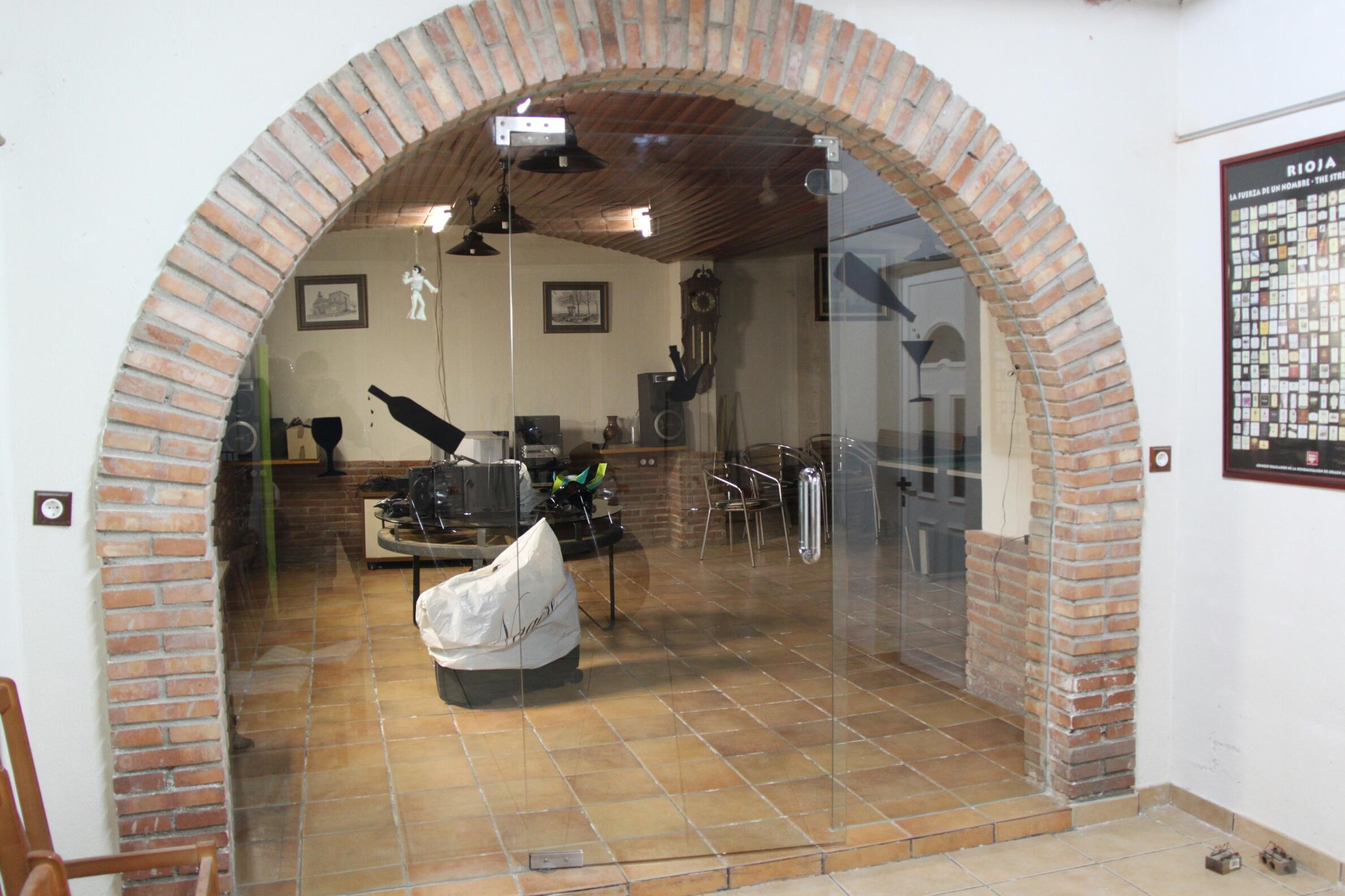 Puerta de vidrio en arco en la bodega de una casa cerca de for Casas con puertas de vidrio